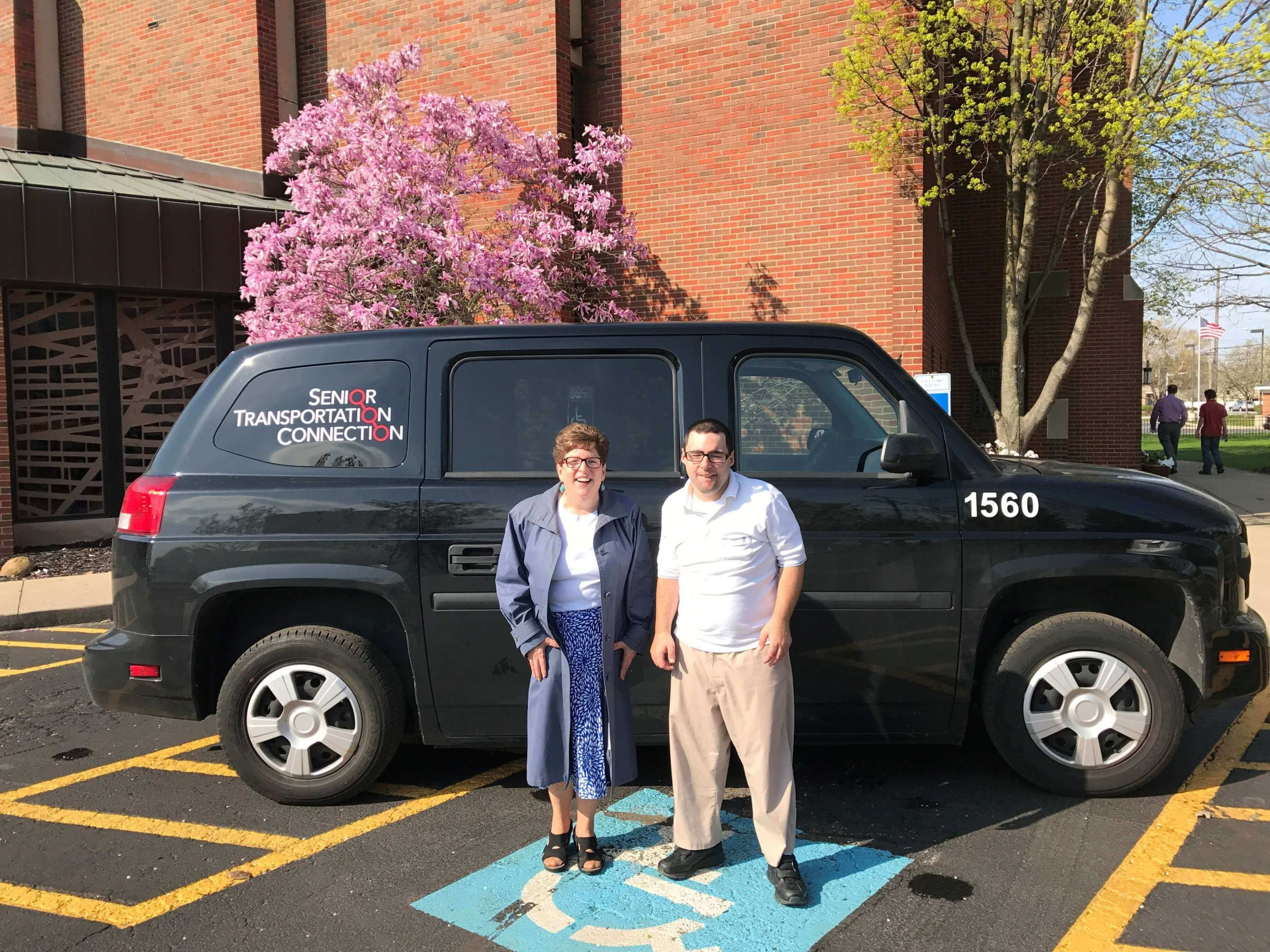 two people in front of the senior transportation connection building