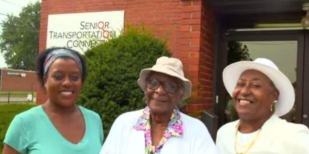 three women in front of the senior transportation connection building